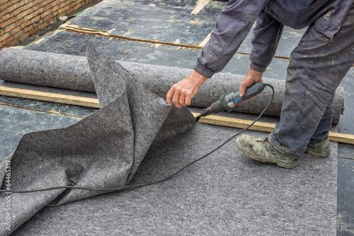 Fotografie, Obraz  Pracovník řezání izolačního materiálu pro základových zdí