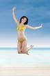 Attractive woman in bikini jumping at beach 1