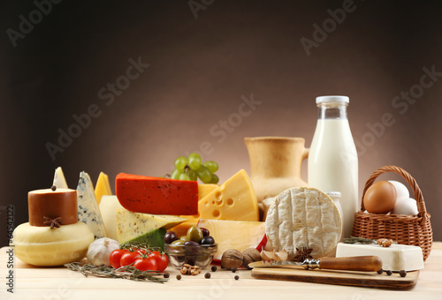 Poster Zuivelproducten Tasty dairy products on wooden table, on dark background