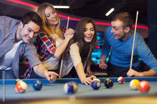 Group of young friends playing billiard Fotobehang