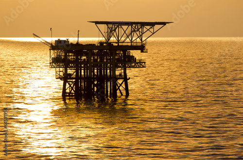 Poster Helicopter Silhouette of an offshore oil rig at sunrise