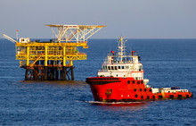 Offshore Drilling Rig And Supply Vessel At Sunset