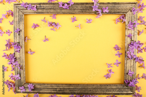 Beautiful lilac flowers and photo frame on yellow background