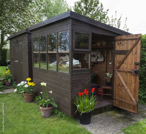Fotomural Garden shed with door open, tools, flowers, and plant pots.