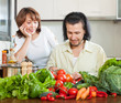 Handsome man and woman with vegetables in the kitchen