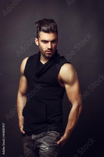 Fotografie, Obraz  Pohledný muž, představující v ateliéru na tmavém pozadí