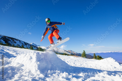 Poster Glisse hiver Snowboarder jumping high from hill in winter