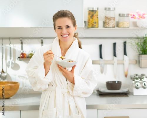 Foto op Plexiglas Bakkerij Portrait of smiling young woman eating muesli in kitchen