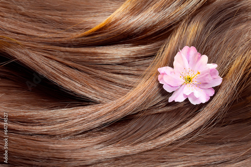 Beautiful healthy shiny hair texture with a flower Fototapeta