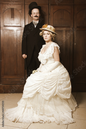 Couple in 19th century garment with woman in dominant role Poster