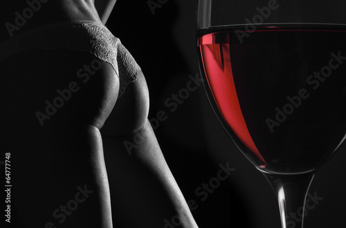 Fotografie, Obraz Beautiful silhouette of a female body and a glass of red wine