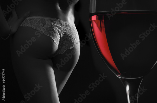 Fotografering  Beautiful silhouette of a female body and a glass of red wine