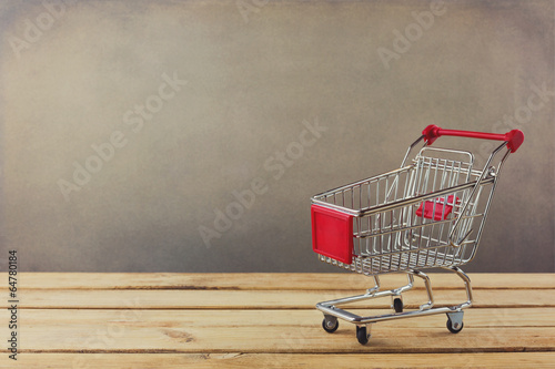 Fotomural Shopping cart on wooden surface