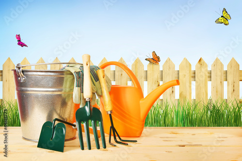 Fototapeta Gardening composition with tools against green grass and wooden obraz