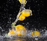 Lemons in water splash on black background