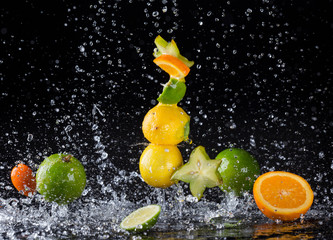 Obraz na Szkle Do baru Citrus fruit in water splash on black background