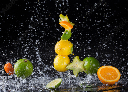 Citrus fruit in water splash on black background - 64818700