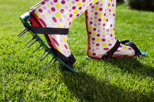 Fényképezés  Woman wearing spiked lawn revitalizing aerating shoes