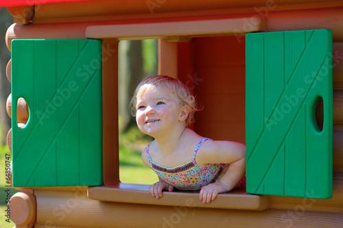Fototapeta Little girl having fun outdoors hiding in plastic playhouse