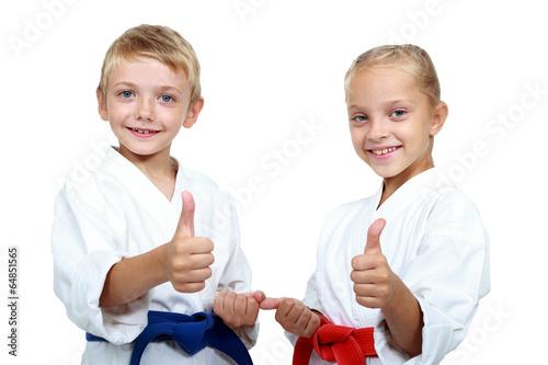Deurstickers Vechtsport Boy and girl in karategi are showing thumb super