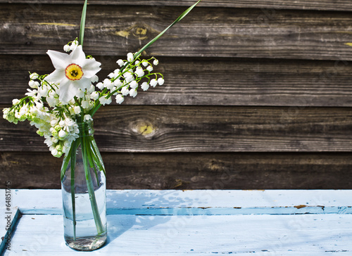 Wall Murals Lily of the valley Bouquet of white spring flowers in a bottle on blue wooden table