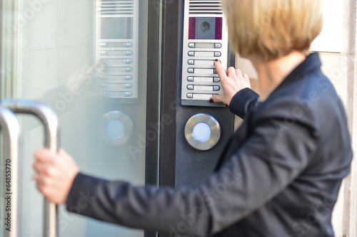Valokuva  Woman pushing a intercom button