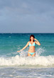 Smiling young redhead woman standing in the ocean wave