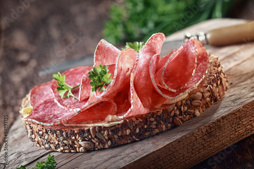 Fototapeta Wholegrain bread with spicy Italian salami obraz