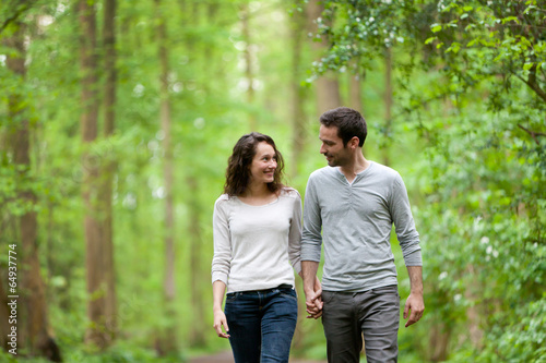 Fotomural Young couple having a walk in a forest