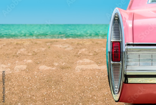 Fotografia  Vintage pink car on the beach