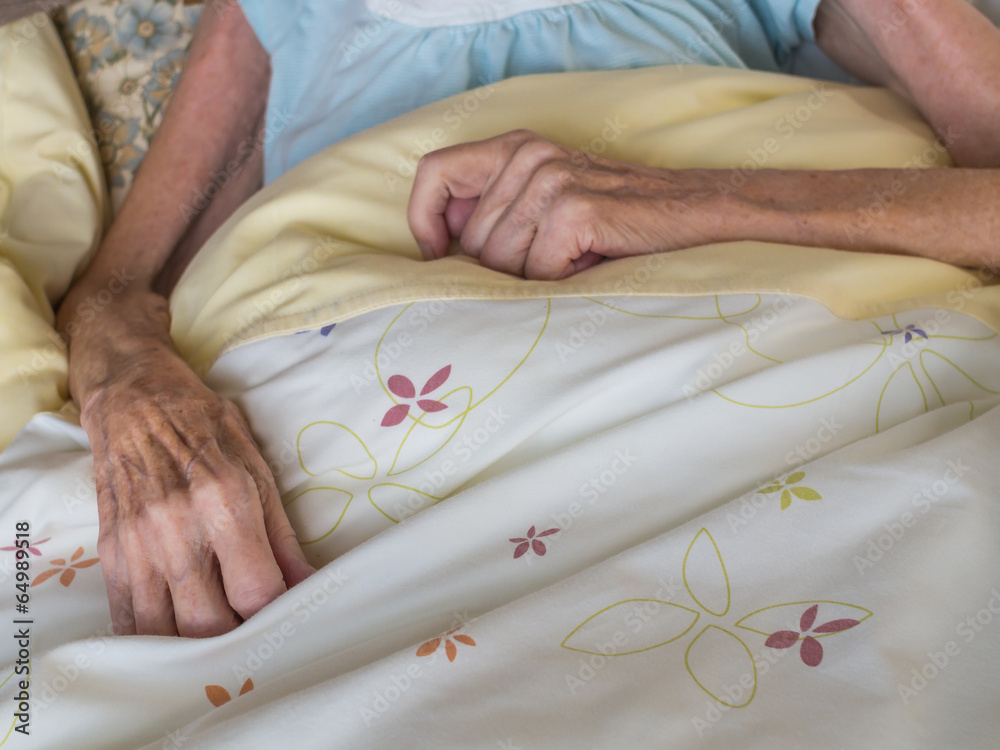 Fototapeta Old woman with very skinny arms and hands lying in a bed