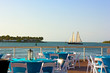 A sea view of dining area with sailboat passing by.