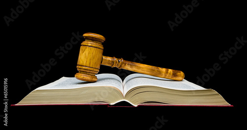 Photo Gavel lies on the open book. black background.
