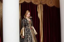 Actress In Royal Dress Posing On Curtain Backdrop