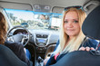Blond hair young woman a passenger looking back when driving car