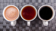 Hot Beverages Of Chocolate, Tea And Black Coffee On Woven Place