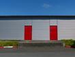 Moderner Hangar mit roten Türen aus Stahl am Segelflugplatz in Oerlinghausen bei Bielefeld am Teutoburger Wald in Ostwestfalen-Lippe