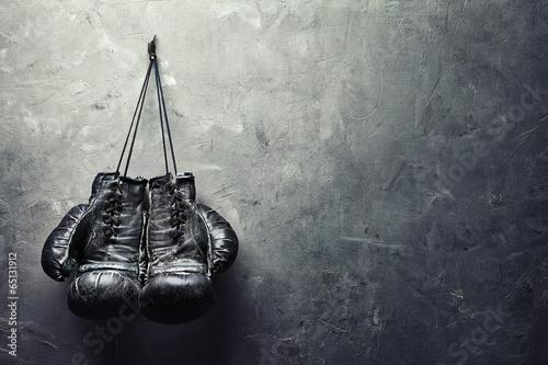 Valokuvatapetti old boxing gloves hang on nail on texture wall