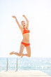 Happy young woman jumping on bridge
