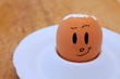 Egg with broken shell and drawn face