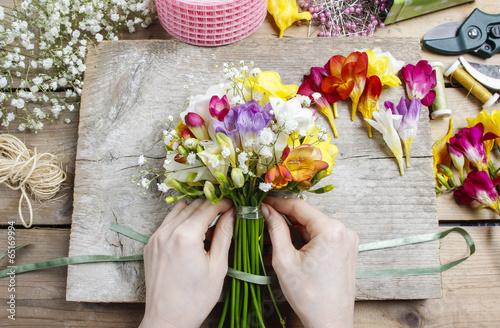 Spoed Foto op Canvas Iris Florist at work. Woman making bouquet of freesia flowers