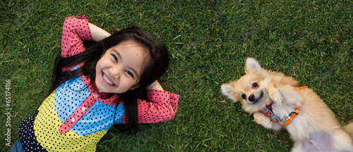 Tableau sur Toile Happy Asian girl with her doggy portrait lying on lawn