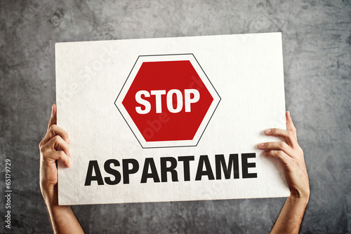 Photo Hands holding banner with STOP ASPARTAME message