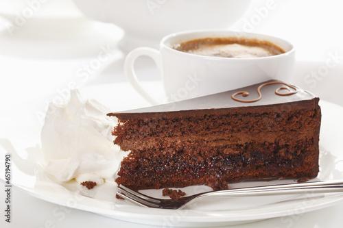 Fotografie, Obraz  Scheibe der Sachertorte in der Platte mit Kaffeetasse im Hintergrund