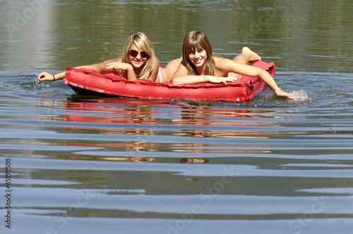 Fotografie, Obraz  Zwei junge Frauen schwimmt auf Luftmatratze