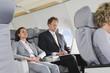 Deutschland,Bayern,München,Geschäftsmann arbeitet am Laptop und Geschäftsfrau ruht in Business-Class- Flugzeug-Kabine