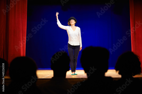 Photo  People watching actress on theater stage during play