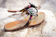 Summer sandals on a sandy beach standing on a rock