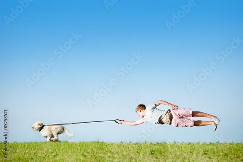 Fotografie, Obraz  Hund an Leine mit fliegendem Hundebesitzer