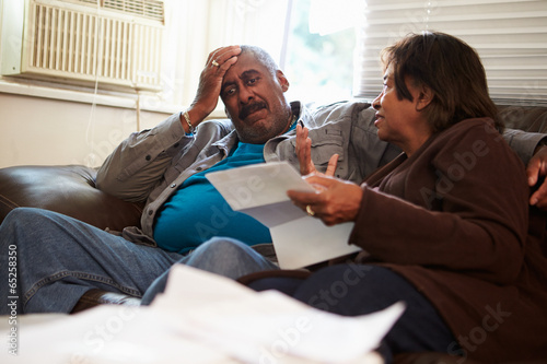 Fotografía  Worried Senior Couple Sitting On Sofa Looking At Bills